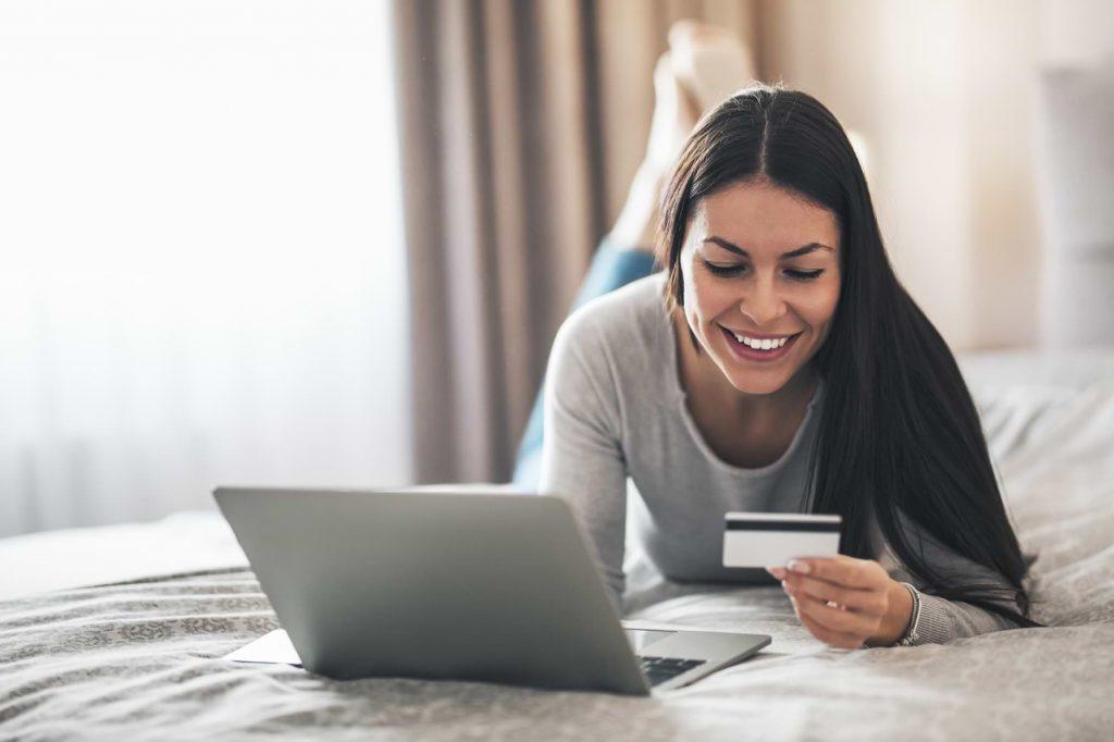 Kvinna med kreditkort som shoppar på datorn